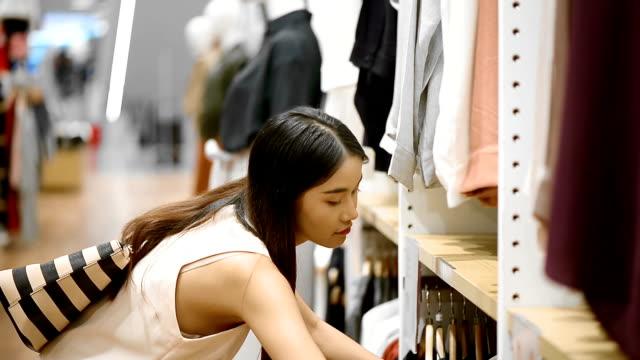 Junge Frau, die Kleidung im Fashion Store betrachten