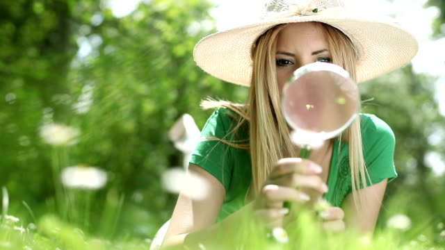 Young woman looking at leaves through a magnifying glass