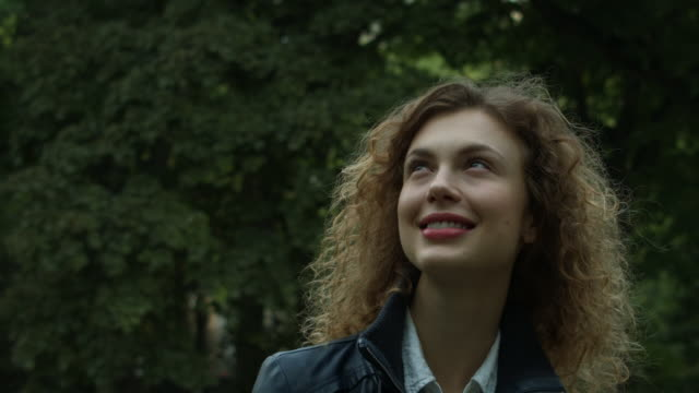 A young woman looking confidently towards the sky outside in New York City in slow motion