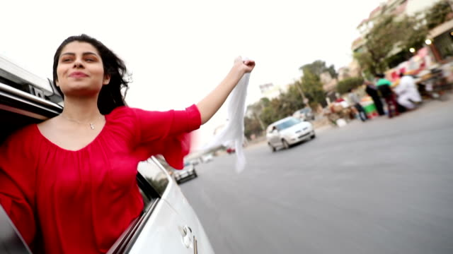 Young woman looking from car window, Delhi, India