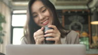 Young woman looking Laptop display with Coffee cup, Slow motion