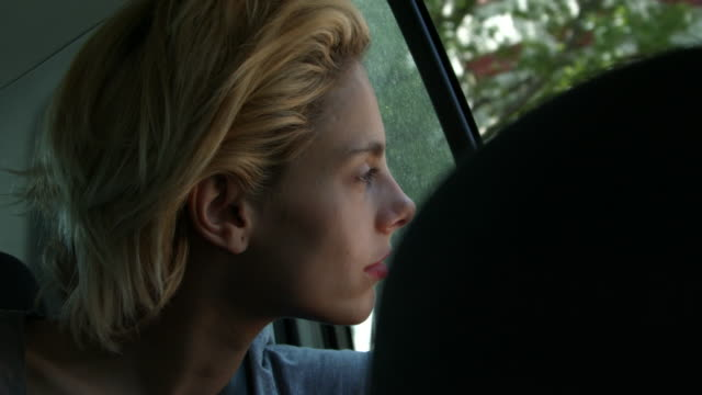 A young woman looking outside a car window while it is moving in New York City