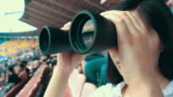 Young woman looking through telescope in stadium