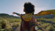 SLO MO. Young woman looks around and waves hand in the air in beautiful Nevada desert.