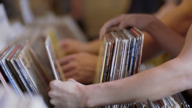 Young woman looks through vintage vinyl with friends in record store and finds treasure
