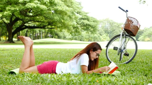 Jonge vrouw liggen en het lezen van een boek in Park