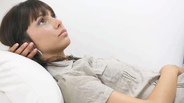 Young woman lying down on sofa and thinking