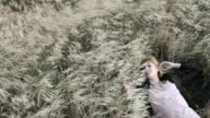 Young woman lying in grassy field