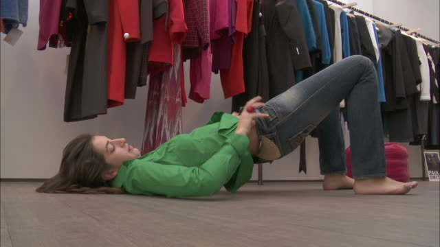 MS Young woman lying on floor and trying on jeans in store / Brussels, Belgium
