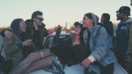 Young woman lying on hood of car and hanging out with friends