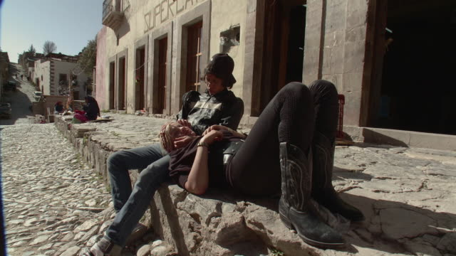 WS Young woman lying on man's lap in cobblestone street / Real de Catorce, San Luis Potosi, Mexico
