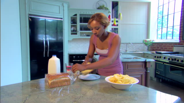 A young woman makes a peanut butter and jelly sandwich.