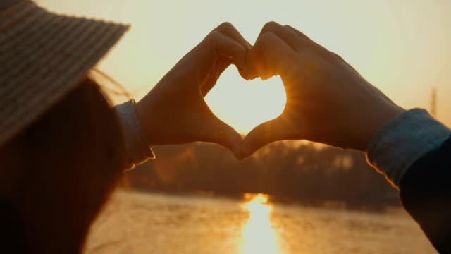 Junge Frau macht eine Herzform bei Sonnenuntergang