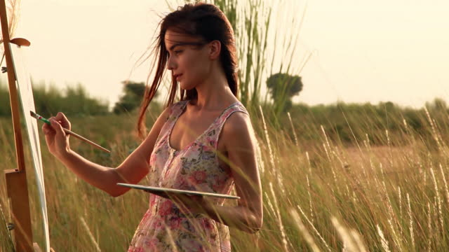 Young woman making a painting on a easel in the forest, Haryana, India