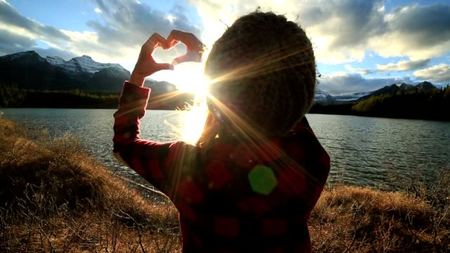 Young woman making heart shape frame with hands to sunset