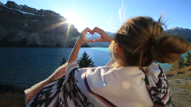 Young woman making heart to spectacular lake mountain scenery