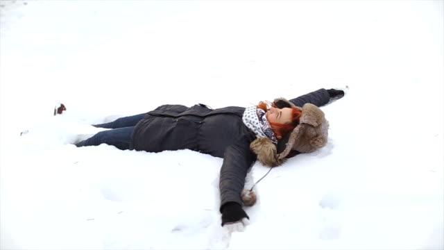Junge Frau machen Schnee-Engel