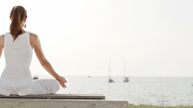 HD DOLLY: Young Woman Meditating By The Sea