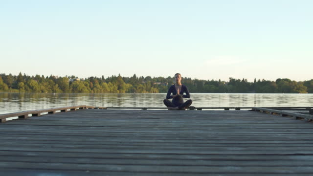 A young woman meditating on a dock