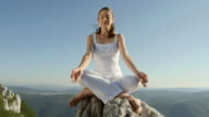 HD DOLLY: Young Woman Meditating On The Rock