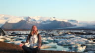 MS Young woman meditating with glacial lagoon in background, Hofn, Iceland