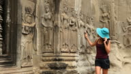 young woman meets celestial deities Angkor Wat Cambodia