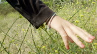 A young woman moves her hand across wild flowers in slow motion.