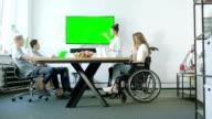Junge Frau auf einen Rollstuhl und ihre Präsentation Team diskutieren mit ihrem Mentor. Startup-Unternehmen