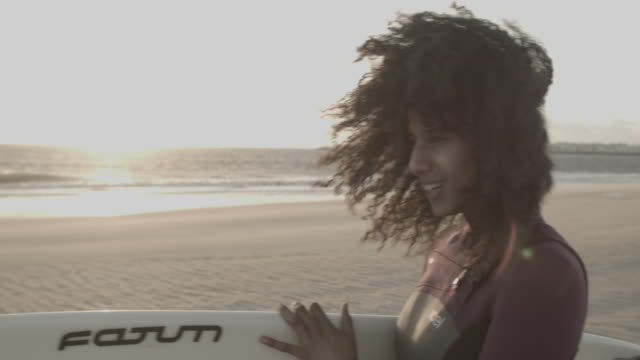 Young woman on beach in Portugal standing by the water with surfboard, smiling