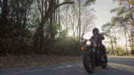 SLO MO. Young woman on motorcycle cruises down empty highway as sun flares through trees.