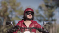 SLO MO. Young woman on motorcycle cruises under tall trees on sunny drive.