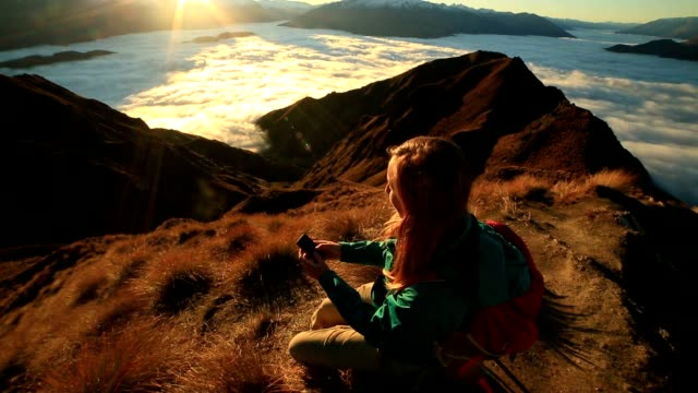 Young woman on mountain top text messaging on mobile phone