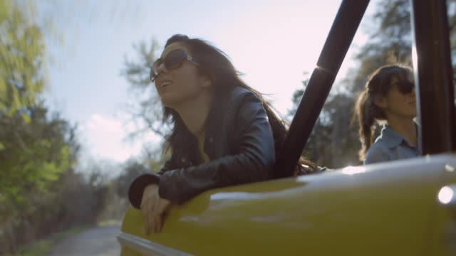 Young woman on road trip smiles as she leans out the back of classic car