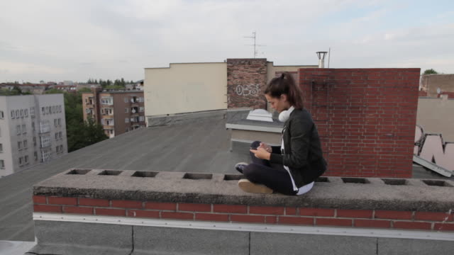 Young woman on rooftop in Berlin, Germany, sitting, taking photographs with smartphone.