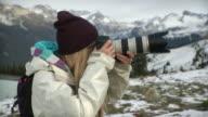 CU Young woman on Whistler mountain taking photos / Whistler, British Columbia, Canada