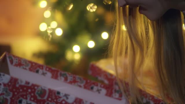 DS MS junge Frau öffnet ein Weihnachtsgeschenk
