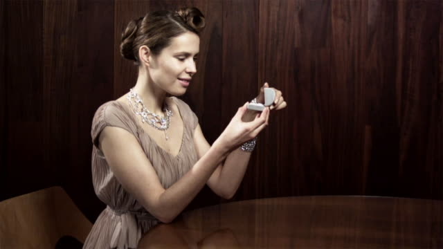 Young woman opening box and putting on ring