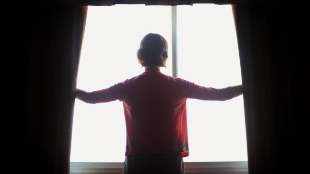 MS Young woman opening curtains in her room / Madison, Wisconsin, USA