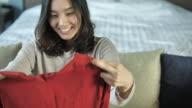 Junge Frau öffnet Karton Einkäufe zu Hause genießen