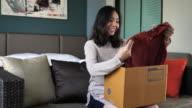 Junge Frau öffnet Karton beim Sitzen auf einem Sofa zu Hause