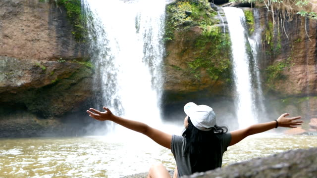 Young woman outstretching arms in front of waterfall