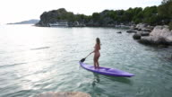 Young woman paddles kayak into bay, standing position