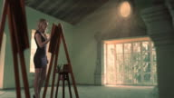 Young woman painting at easel indoors