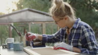 Young woman painting old furniture