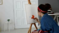 Young woman painting with oil paint
