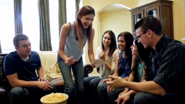 Young woman performing during game of charades with family