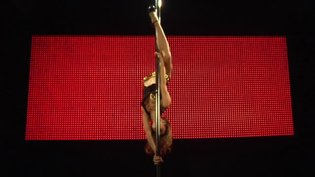 WS SLO MO Young woman performing pole dance on stage / London, UK