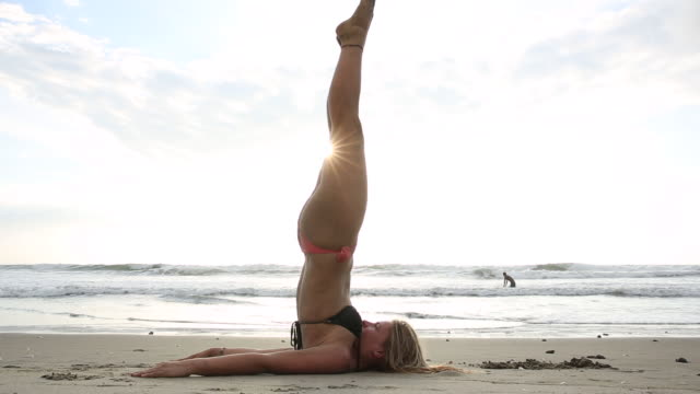 Young woman performs yoga moves on the beach