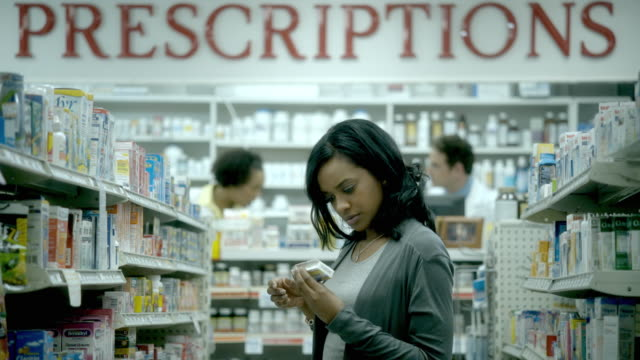MS, R/F, Young woman pharmacy medicine aisle, two pharmacists in background, Scotch Plains, New Jersey, USA