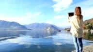Jonge vrouw fotograferen landschap aan het meer